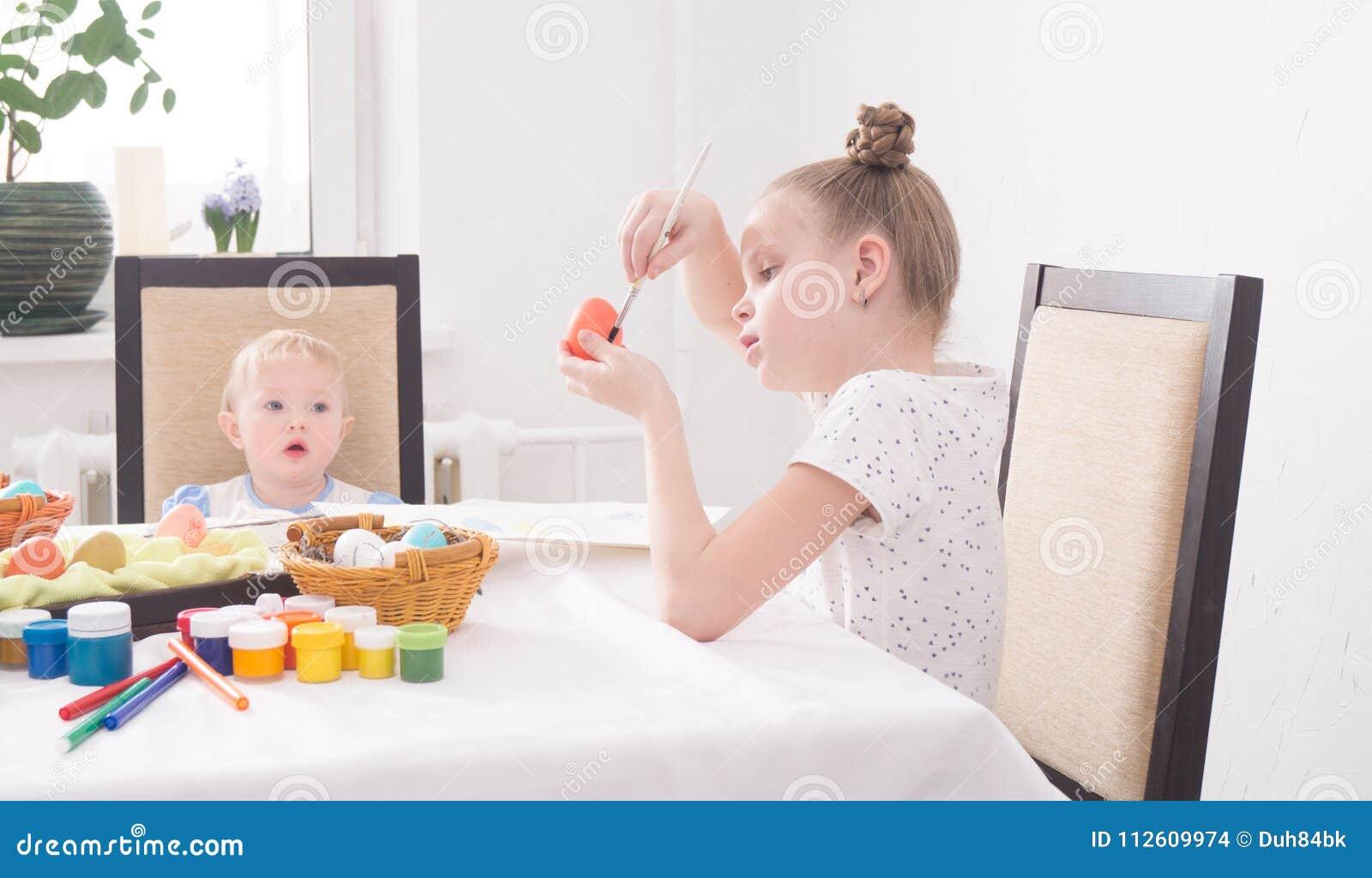 Wielkanoc w rodzinnym okręgu: Dziewczyna maluje Wielkanocnego jajko Młodzi siostra zegarki z entuzjazmem
