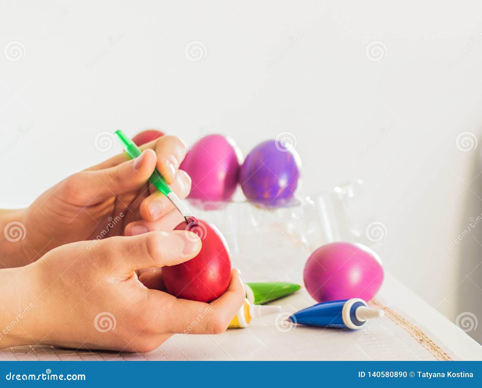 Wielkanocnego jajka kolorystyki proces z muśnięciem akrylowe farby, ręki akcja na białym stole na białym tle pokój