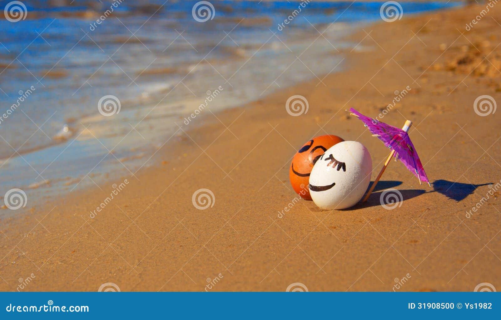 Wielkanocni śmieszni jajka pod parasolem na plaży