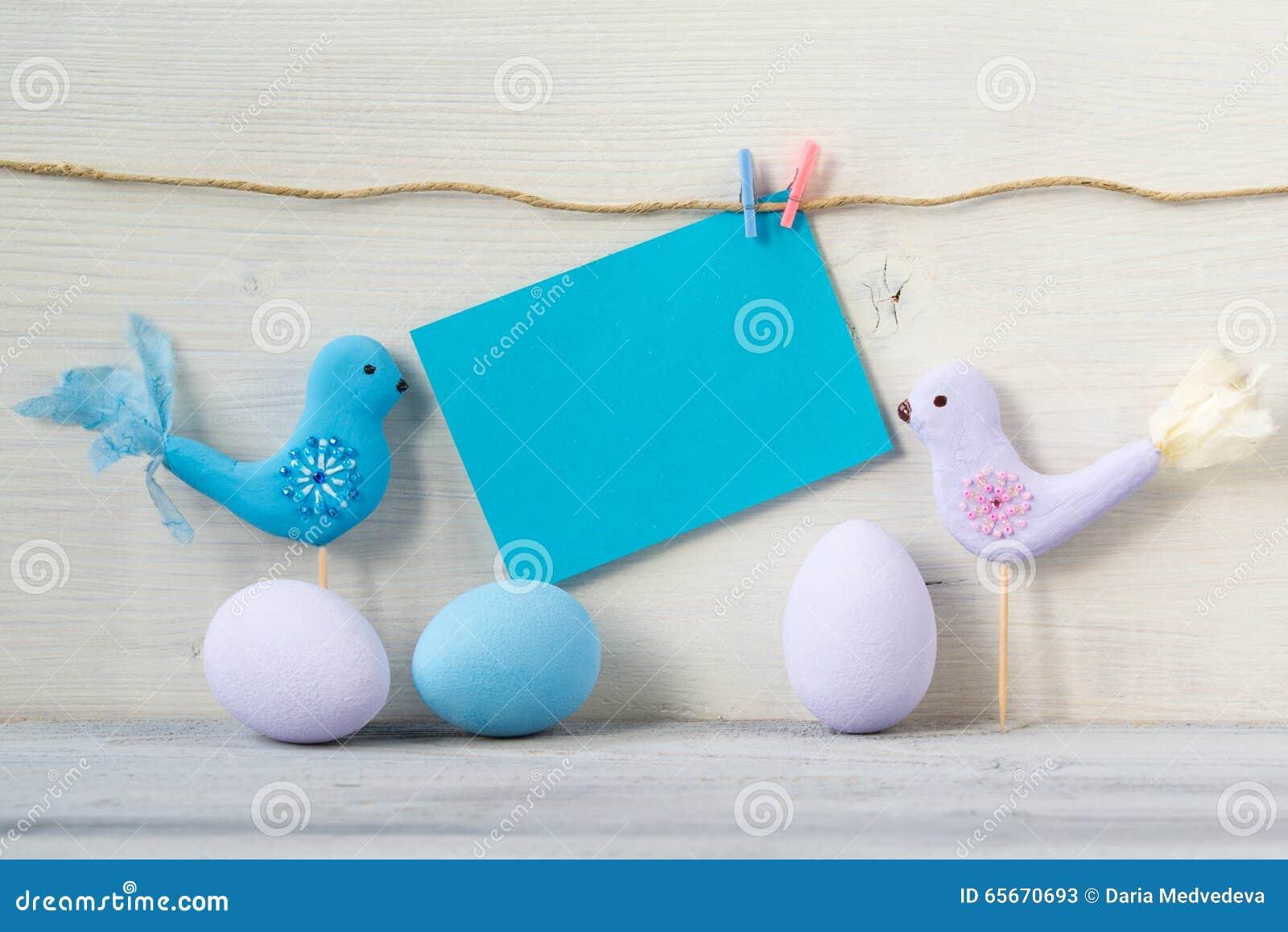 Wielkanocni jajka i dwa ptaka w pastelowych kolorach z pustą błękit kartą na białym drewnianym tle