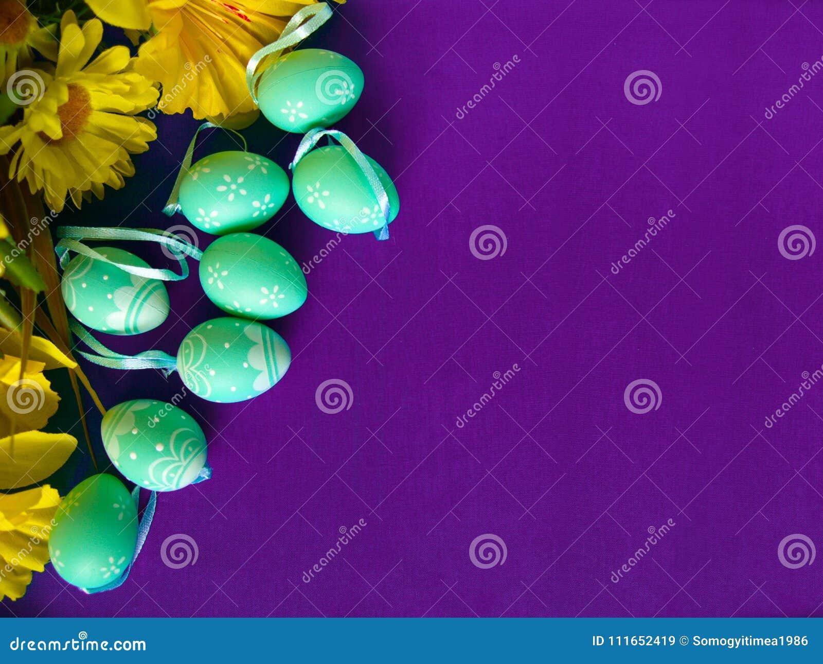 Wielkanocni jajka na purpurowym jedwabiu z żółtymi kwiatami,