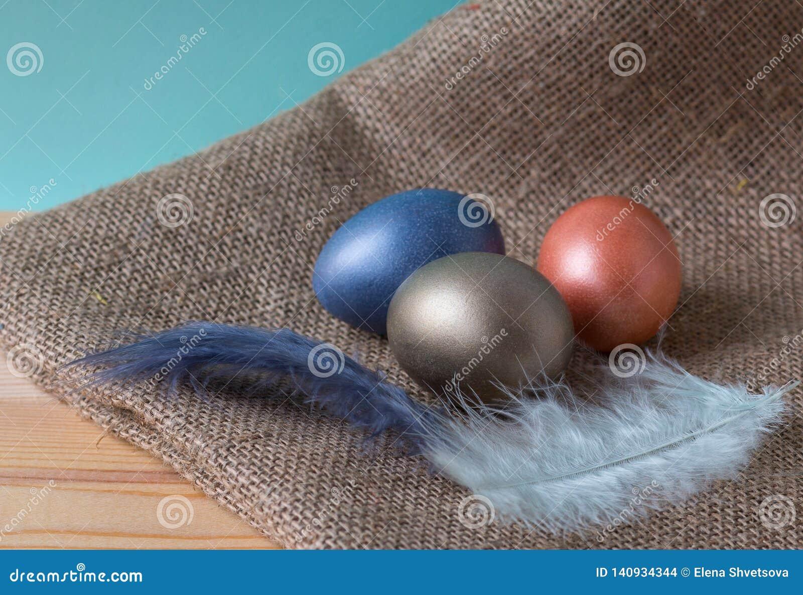 Wielkanocni jajka trzy koloru na burlap na drewnianym stole