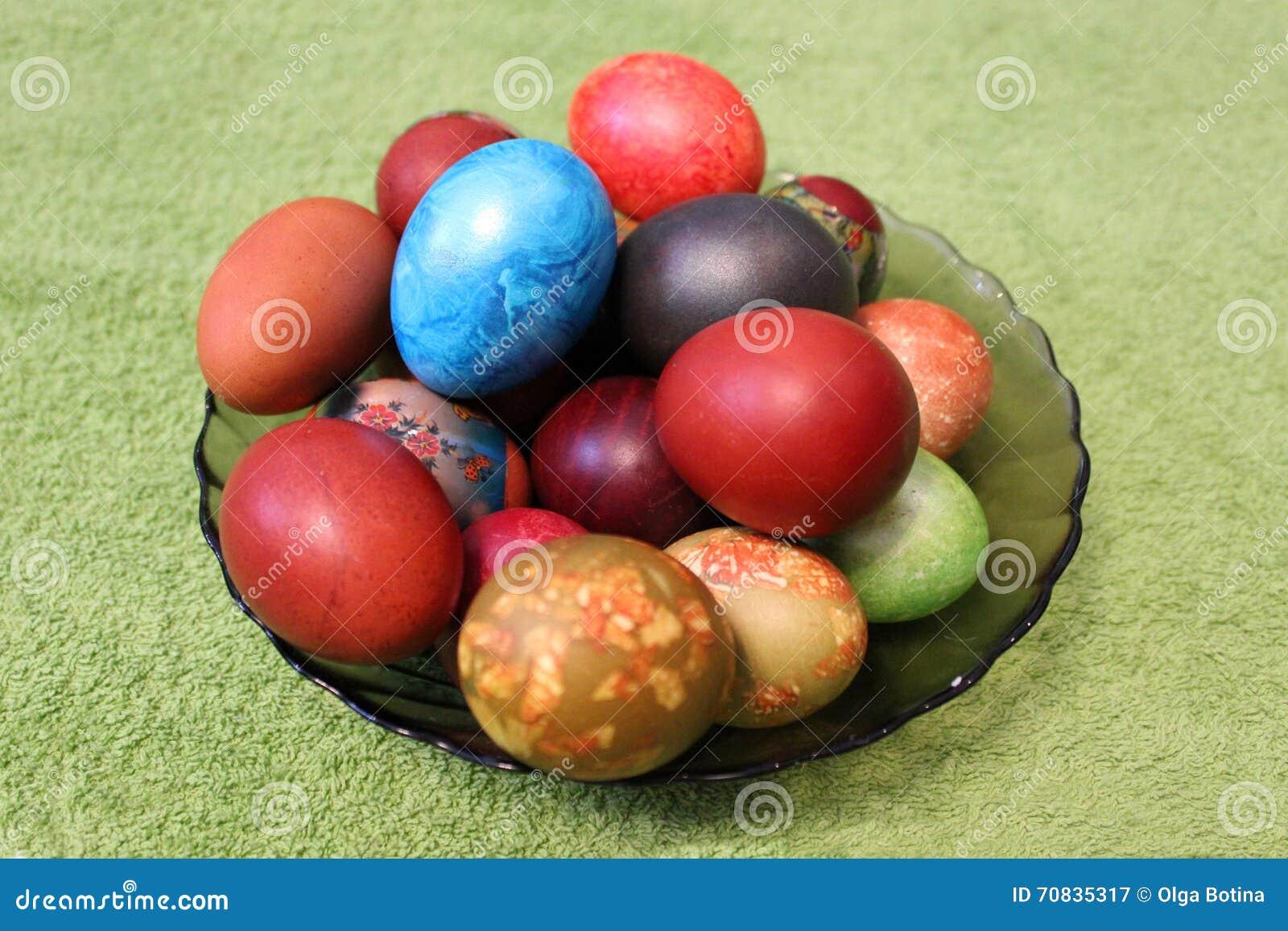 Wielkanocni jajka w talerzu na zielonym tle