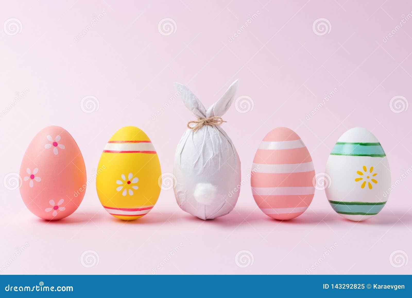 Wielkanocny jajko zawijający w papierze w formie królika z kolorowymi Wielkanocnymi jajkami Minimalny Easter pojęcie