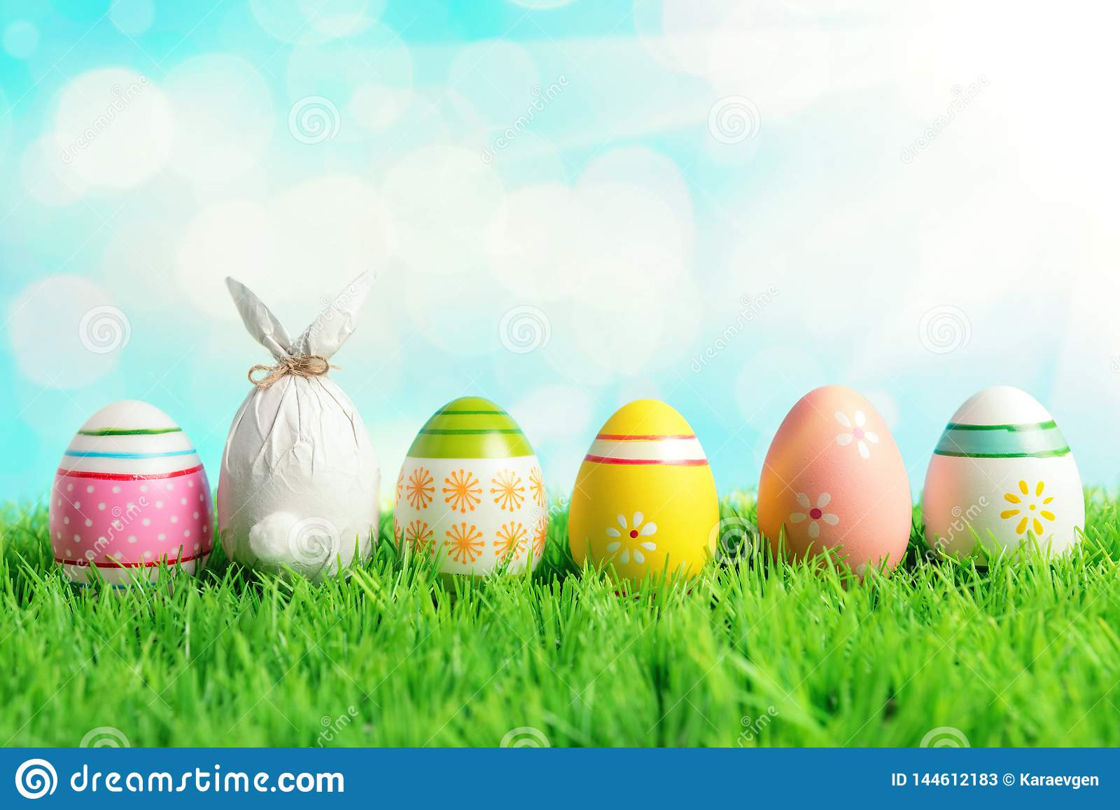 Wielkanocny jajko zawijający w papierze w formie królika z kolorowymi Wielkanocnymi jajkami na zielonej trawie Wiosna wakacji poj