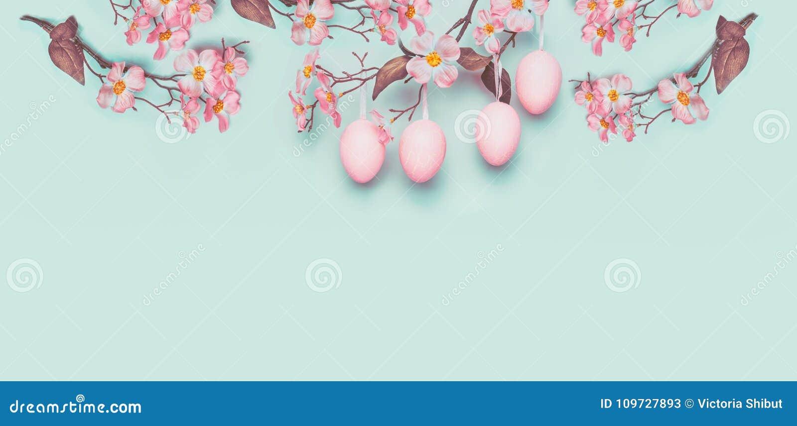Wielkanocny sztandar z wieszać pastelowych menchii Wielkanocnych jajka i wiosna kwitniemy przy światłem przy błękitnym turkusowym