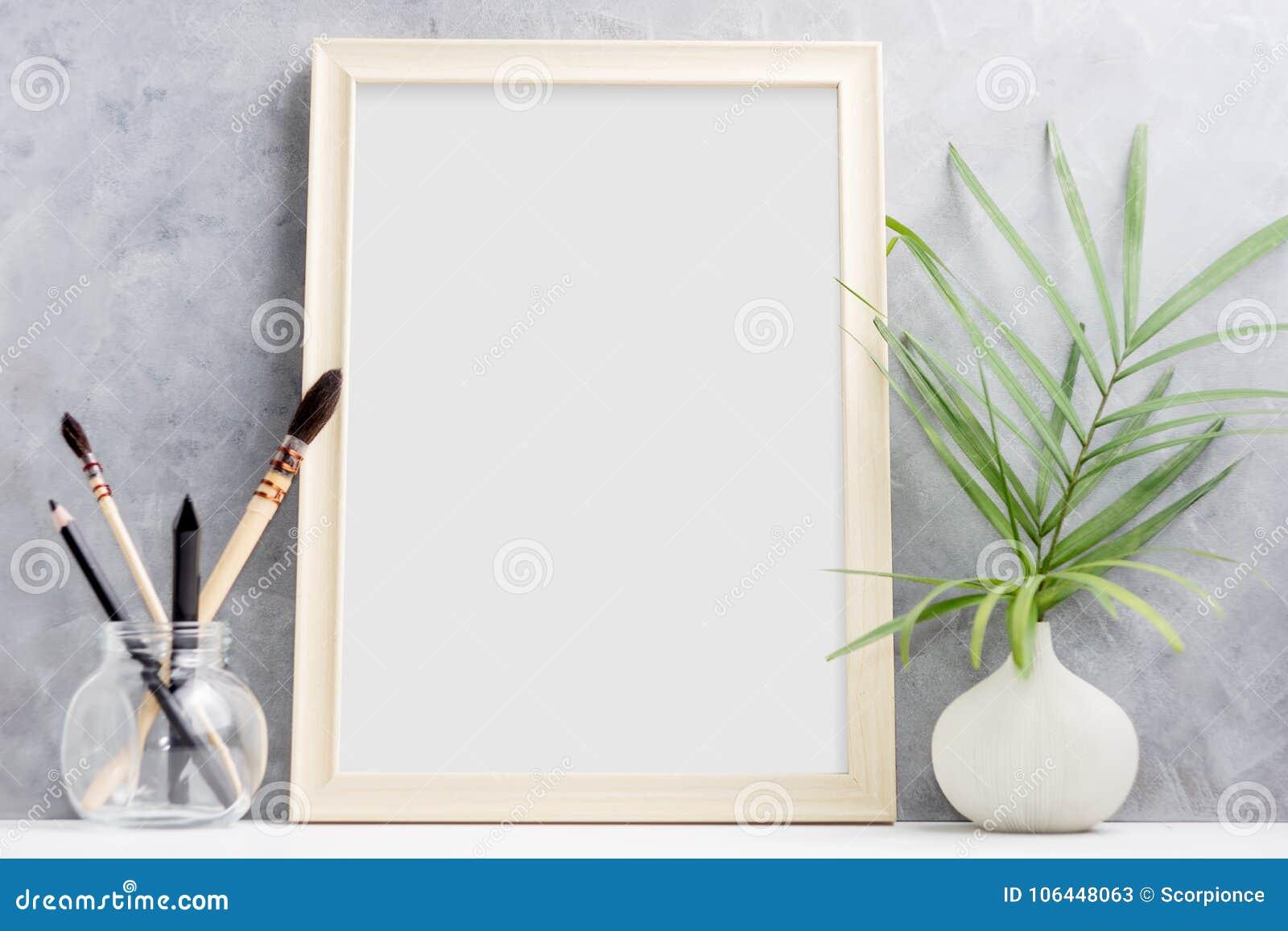 Wielki drewniany fotografii ramy egzamin próbny up szczotkuje w szkle na półce z zieloną palmą i Skandynawa styl