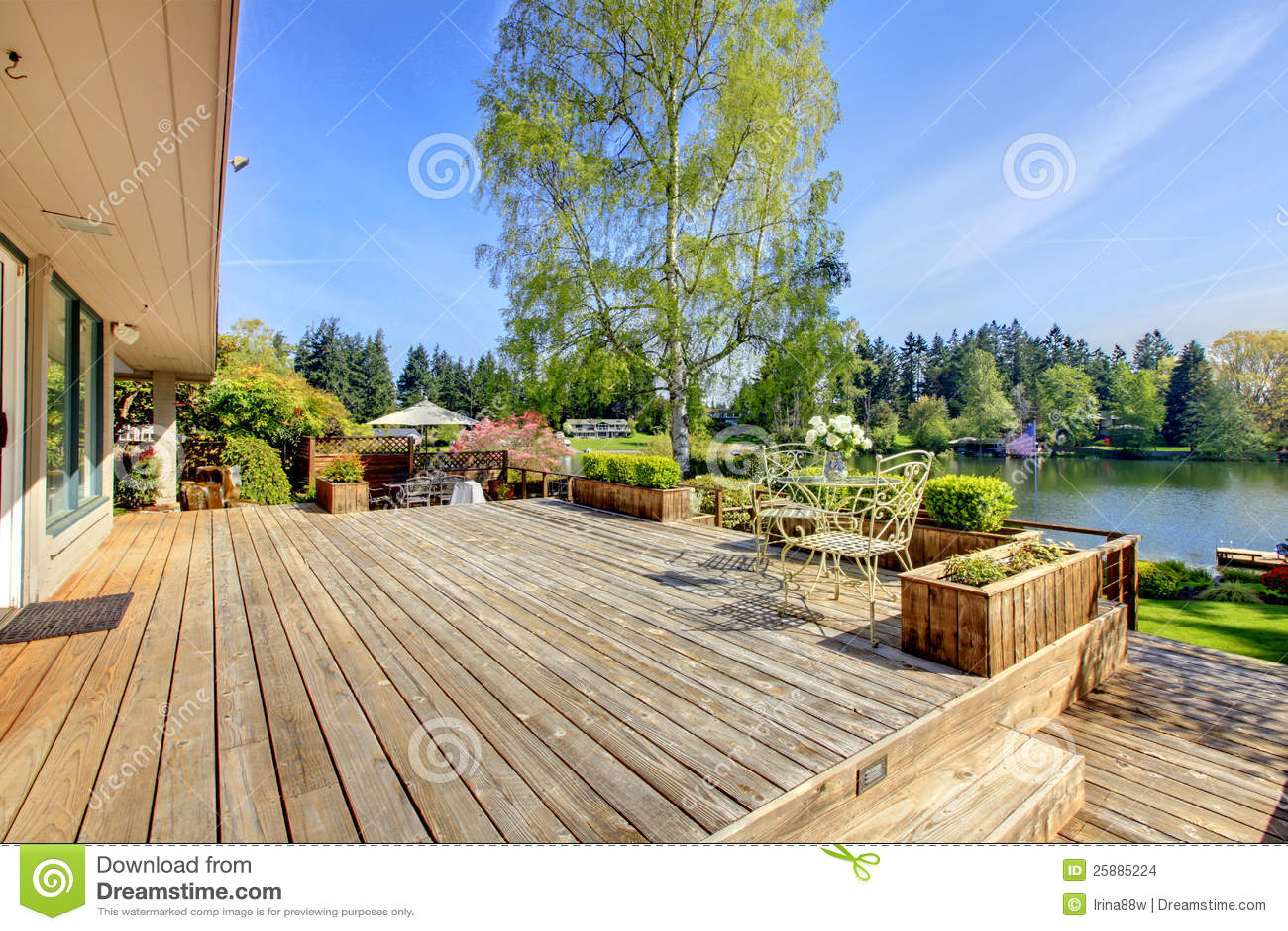 Wielki drewniany pokład z jeziorem i wiosna krajobrazem.