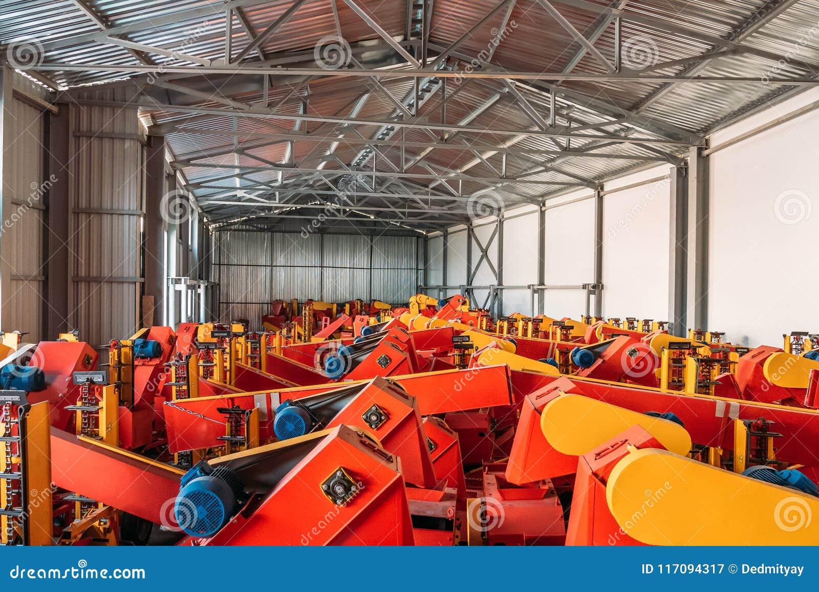Wielki przestronny hangar lub magazyn z przemysłowymi rolniczymi maszynami i syndykatami