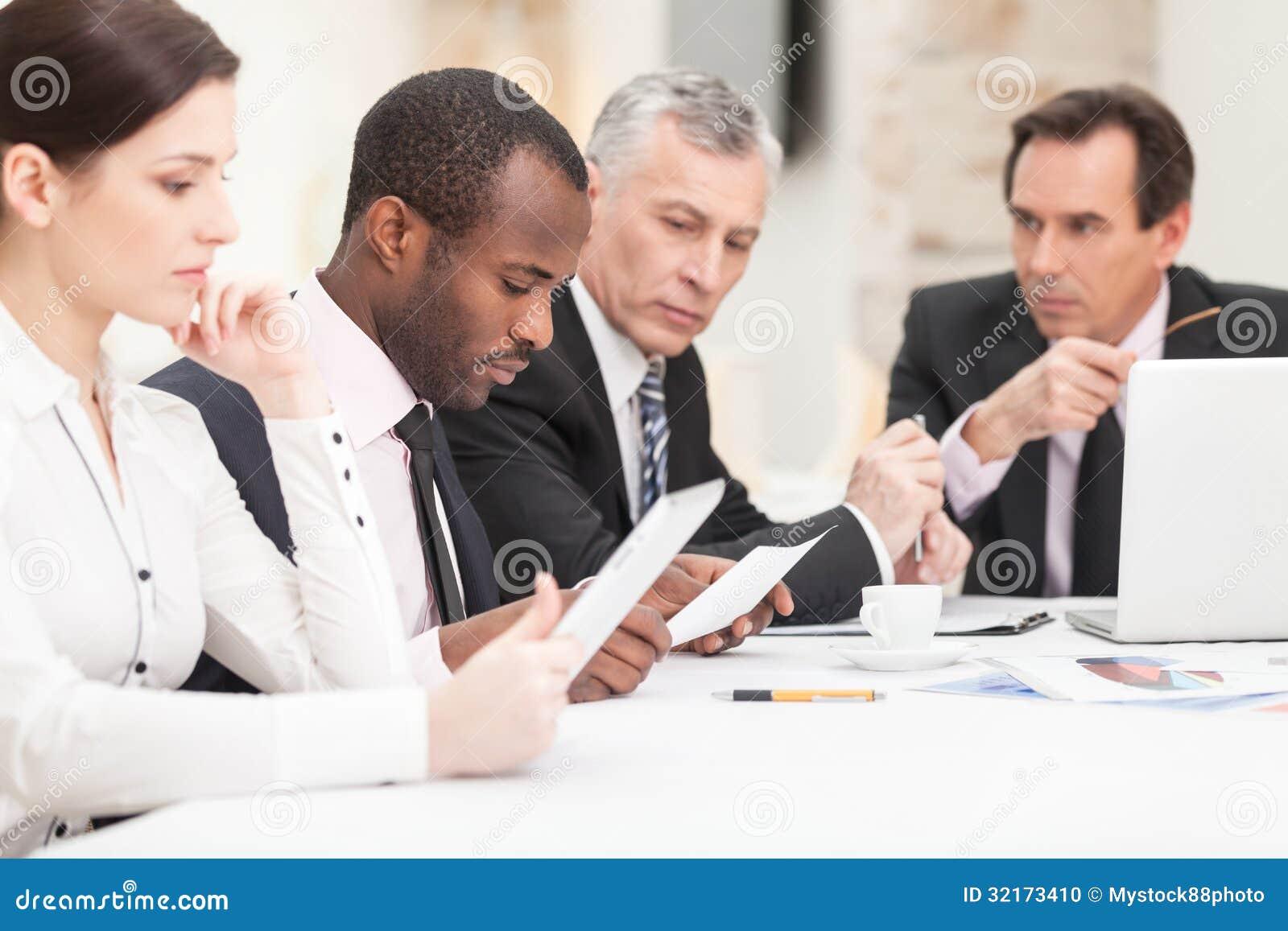 Wielo- etniczni ludzie biznesu dyskutuje pracę