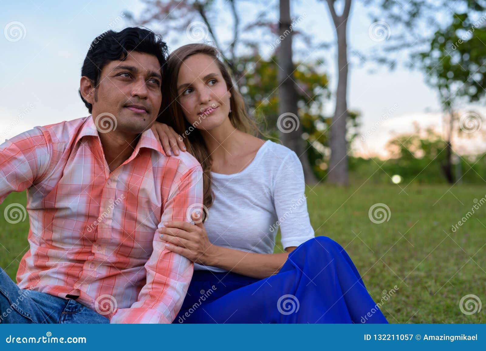 Wielo- etniczny pary obsiadanie, główkowanie na łące i wewnątrz kochamy a