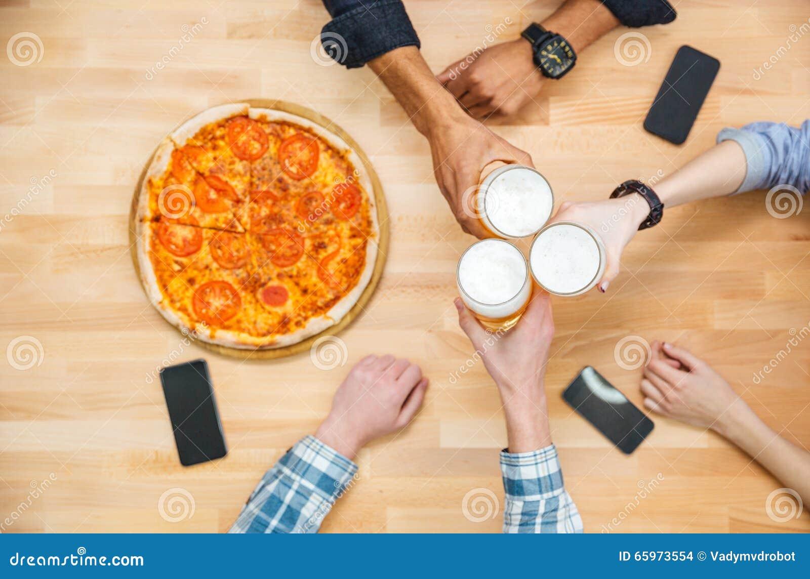 Wieloetniczna grupa młodzi ludzie pije piwo i je pizzę