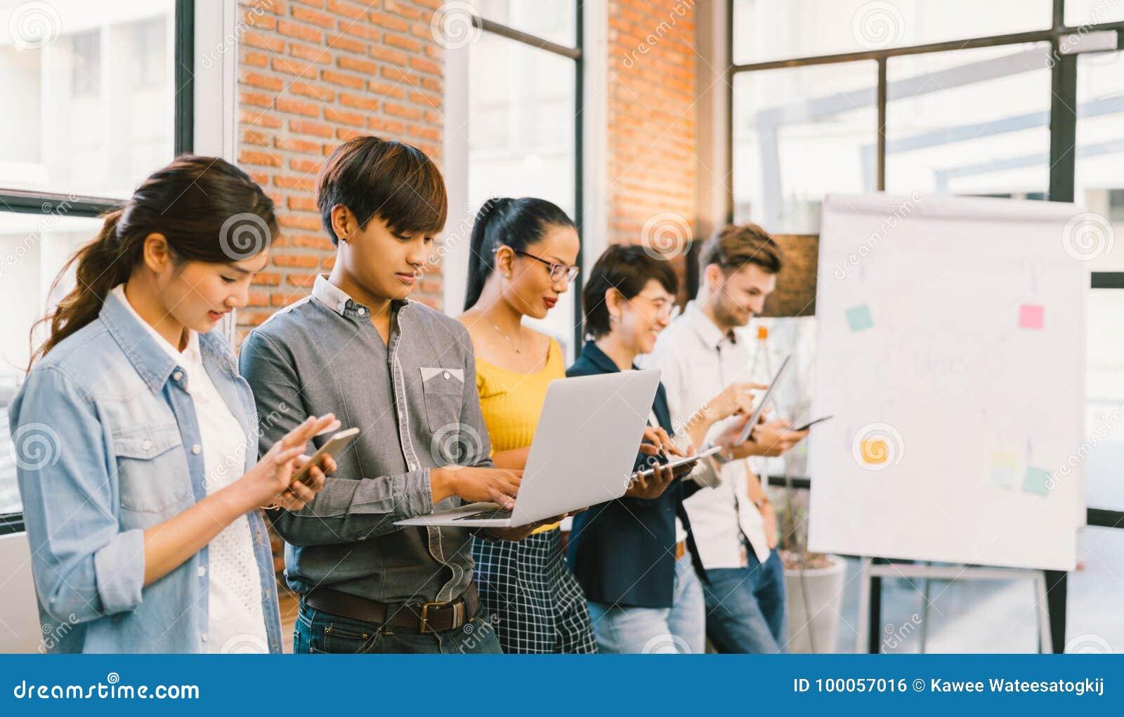 Wieloetniczna różnorodna grupa szczęśliwy młody dorosły używa technologie informacyjne gadżetu przyrząda wpólnie pojęcia leżanki