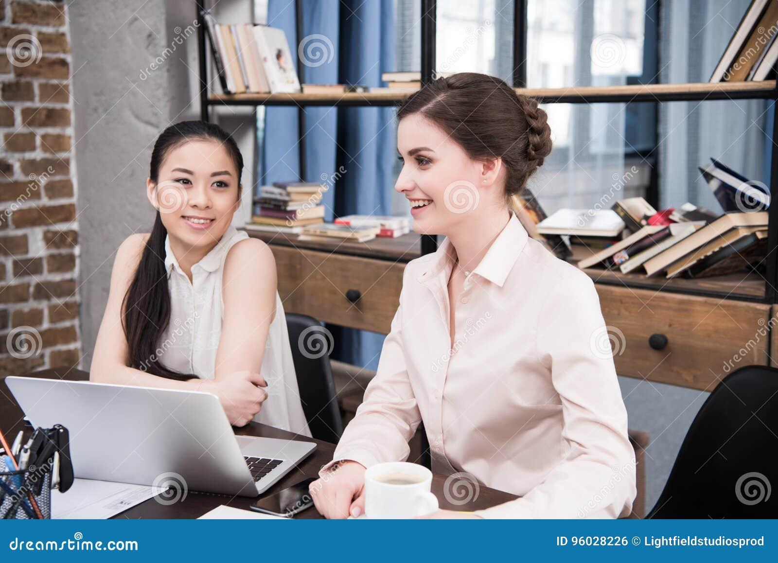 Wielokulturowi bizneswomany dyskutuje projekt przy miejscem pracy z laptopem w nowożytnym biurze