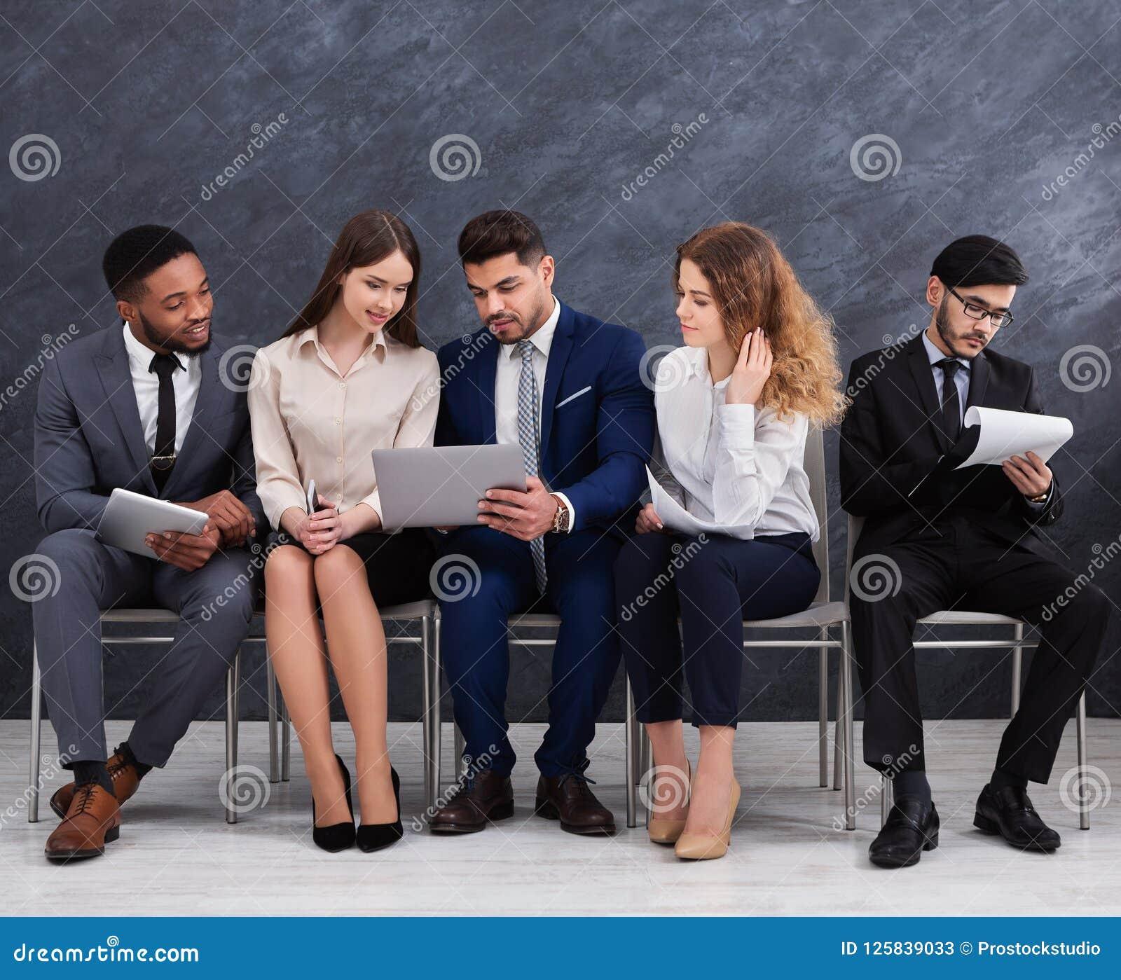 Wielokulturowi młodzi biznesmeni używa laptopy i smartphones