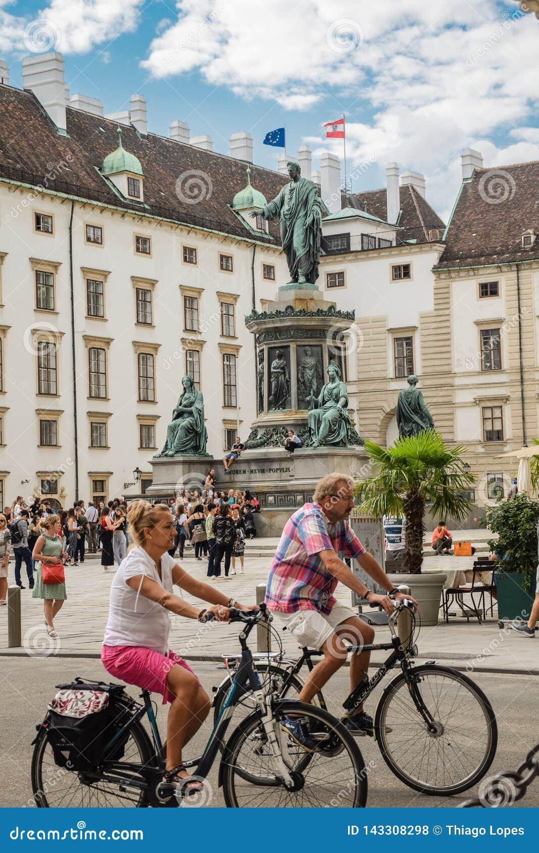 Wien Österrike - September, 15, 2019: Cyklistpar framme av monumentet till Francis II i en borggård som omges av