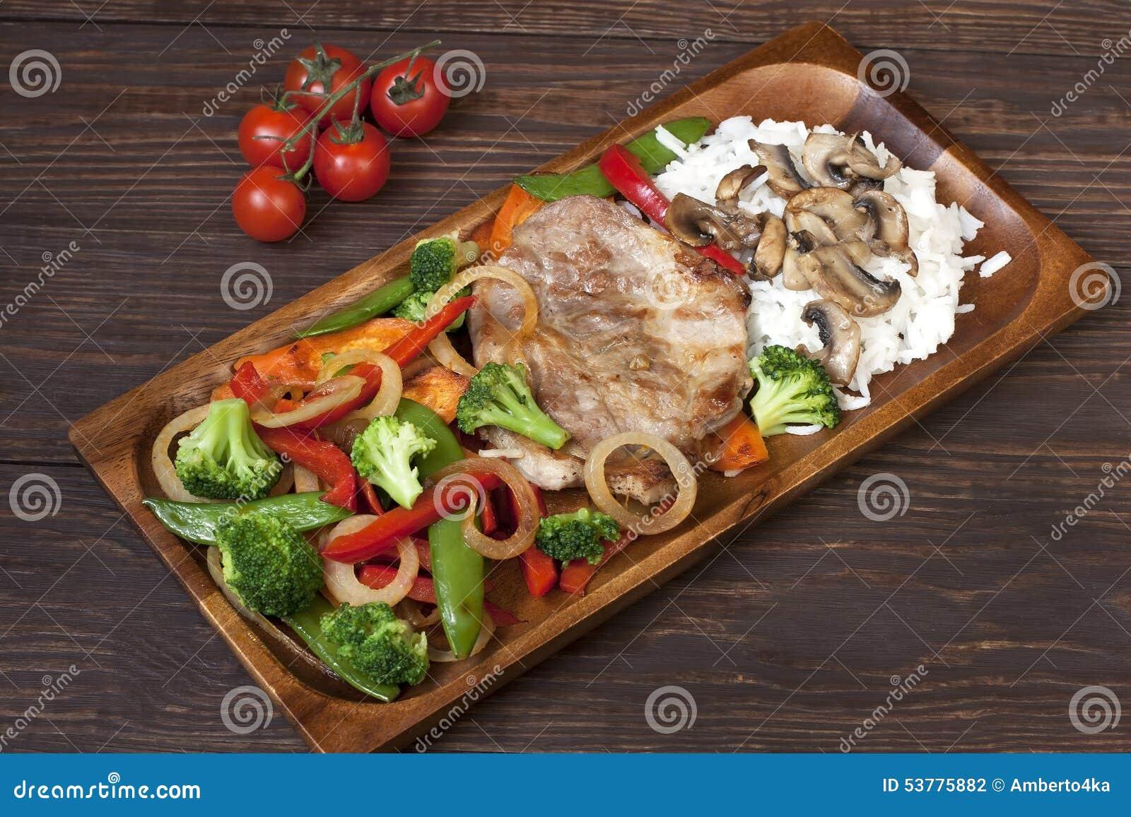 Wieprzowiny mięso piec na grillu z świeżym warzywem na talerzu