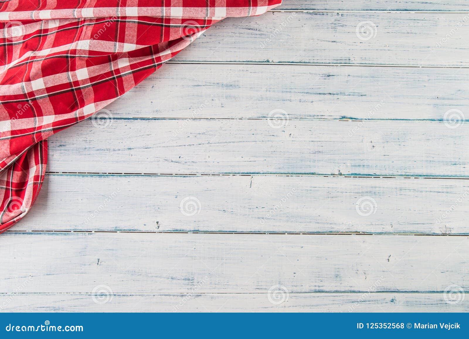 Wierzchołek widoku czerwony w kratkę tablecloth na drewnianym stole