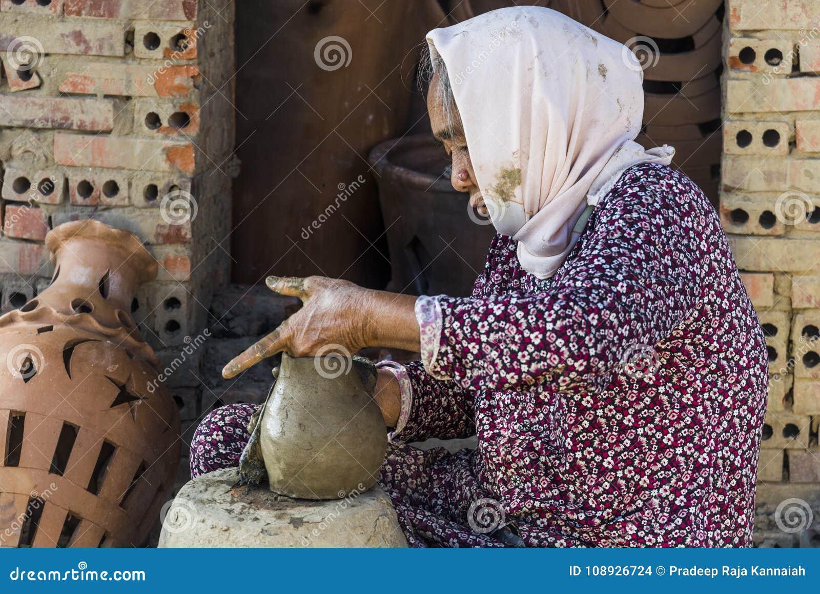 Wietnam Grudzień 2017: Lokalny Wietnamski kobiety formierstwa garnek od glinianej mikstury w jej fabryce, Wietnam