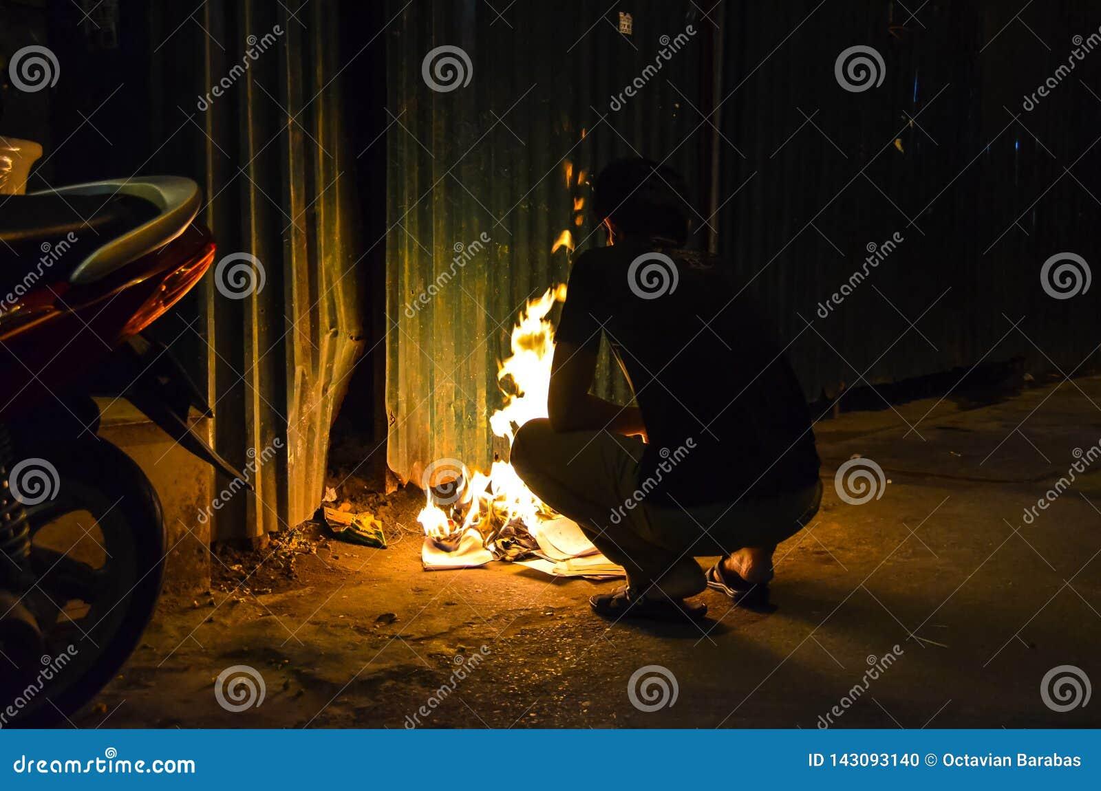 Wietnamski faceta palenia papier przy nocą
