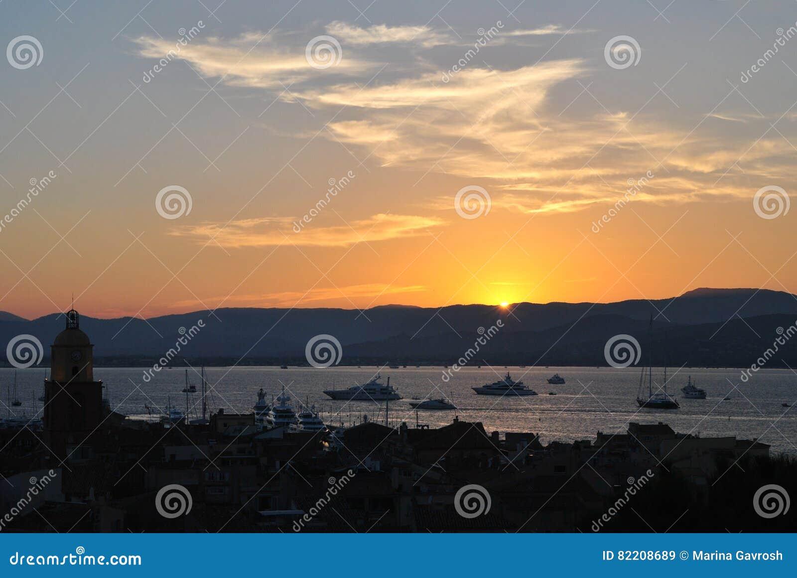 Wiew городка St Tropez старого на предпосылке неба захода солнца