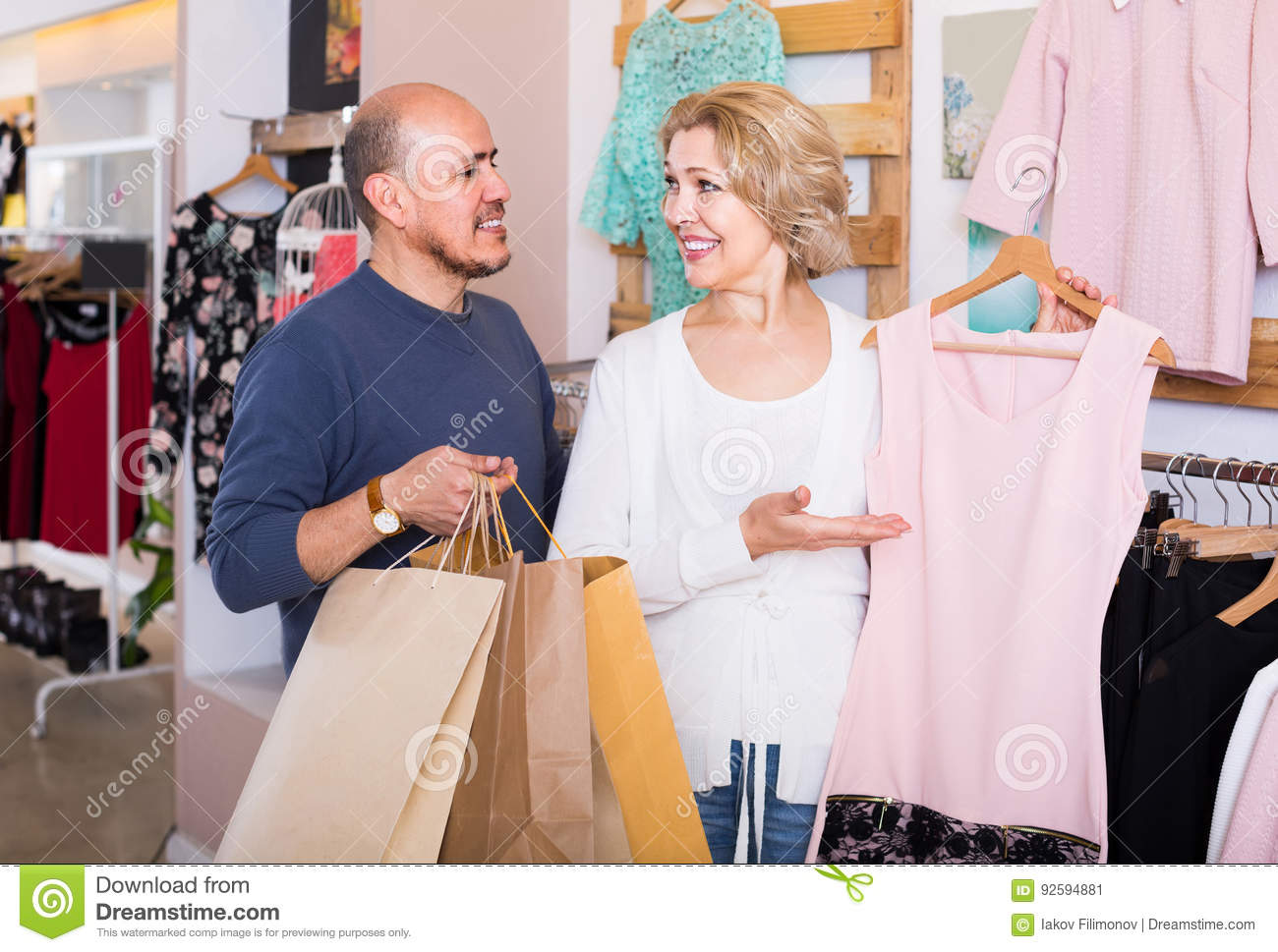 Wife Buying Dress At Apparel Store, Man Is Bored Stock Image - Image