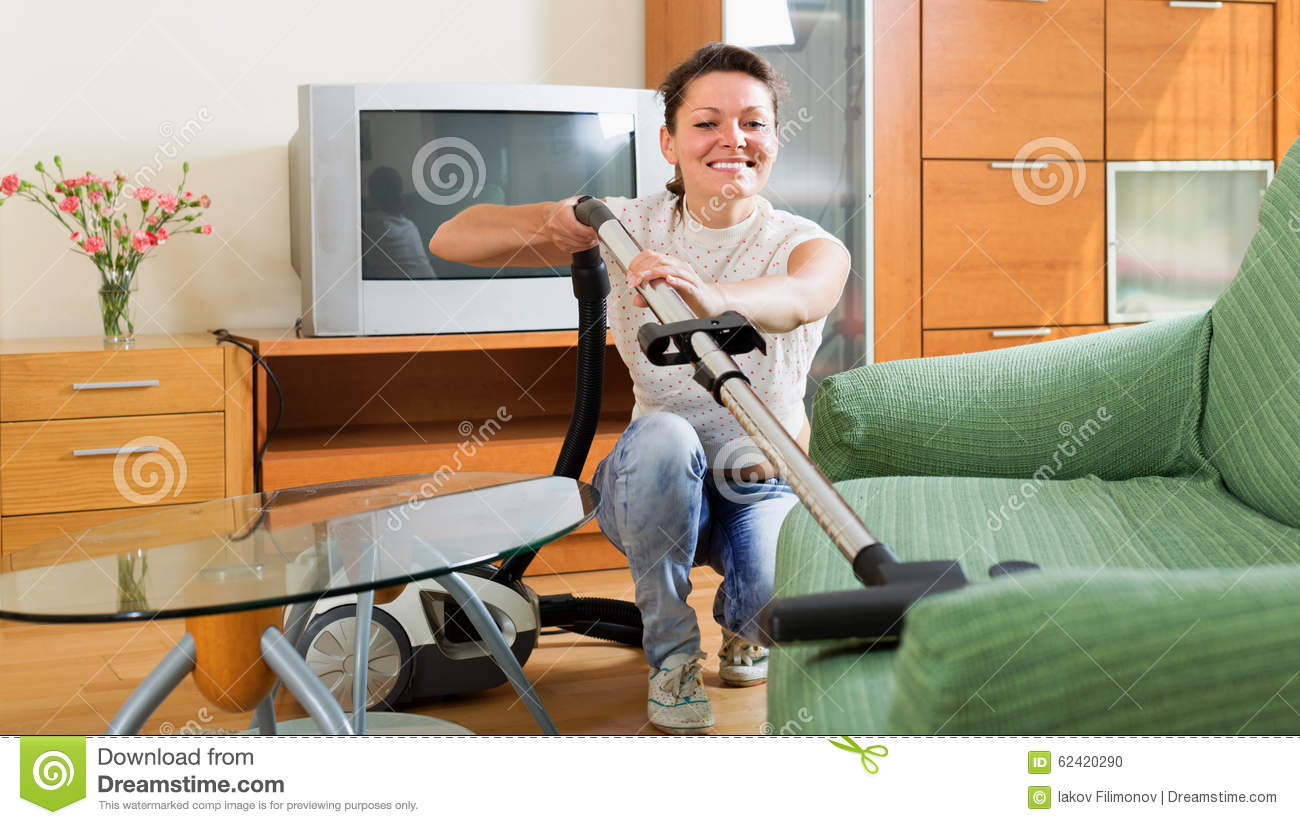 wife cleaning sofa with vacuum cleaner stock photo