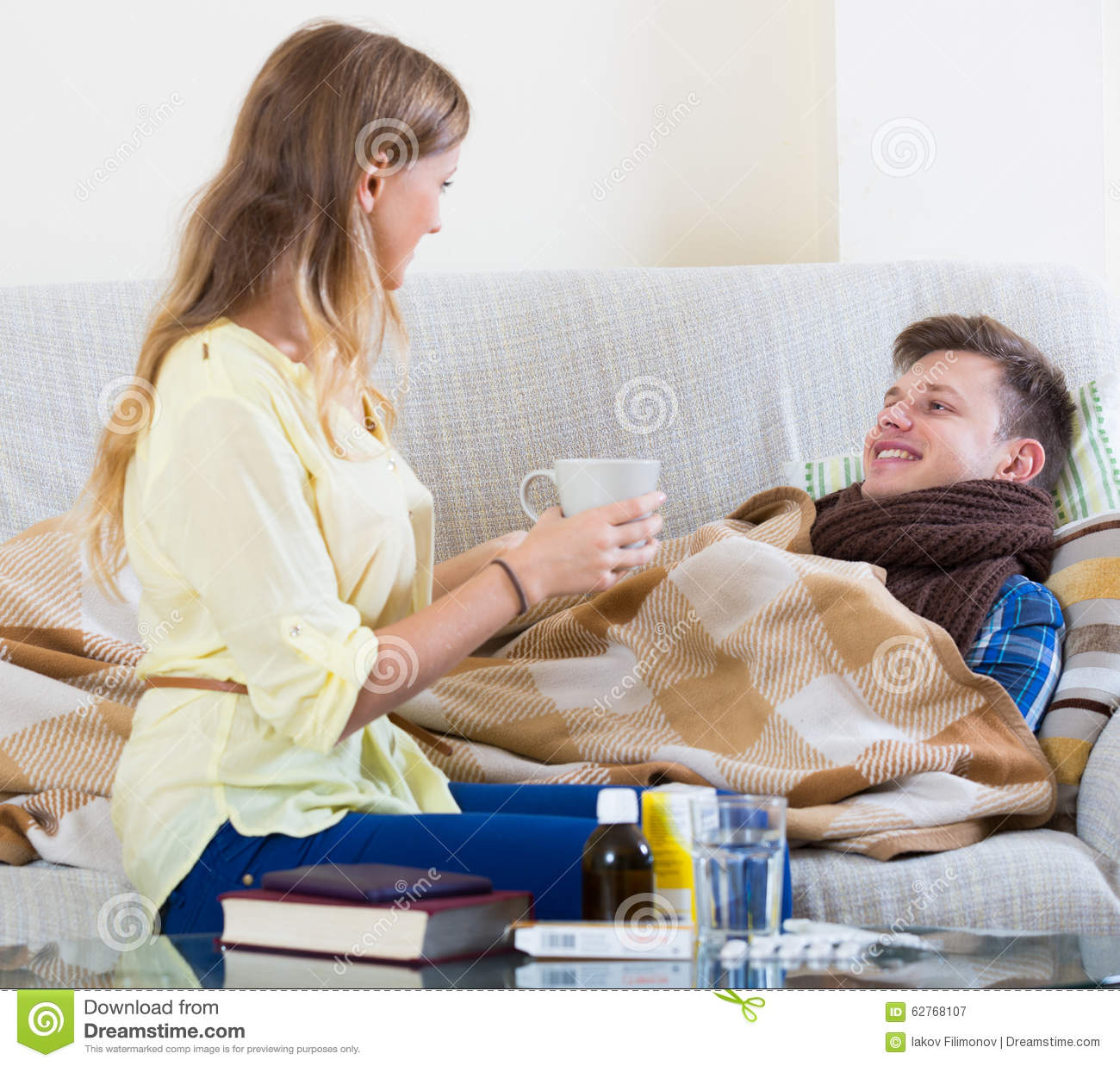 Wife Taking Care Of Young Husband With Flue At Home Stock