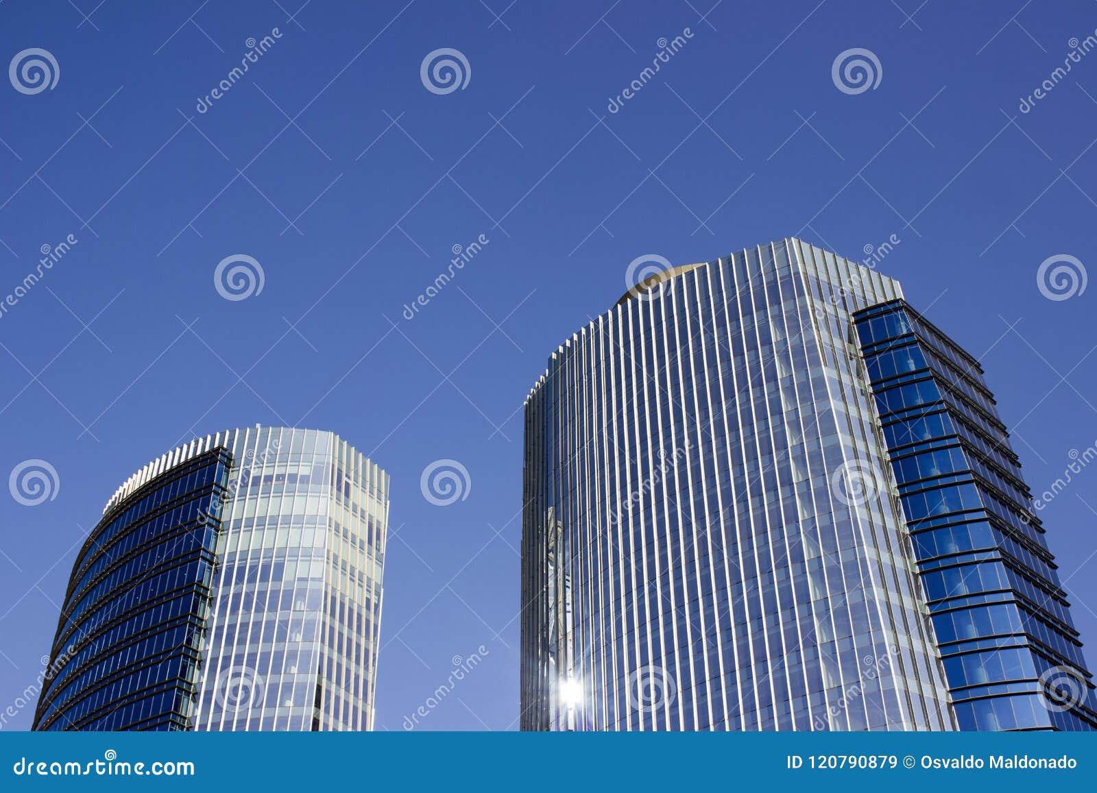 Wijd geschoten van een paar high-rise van het tweelingen collectieve blauwe bureau gebouwen met een gestreept ontwerp