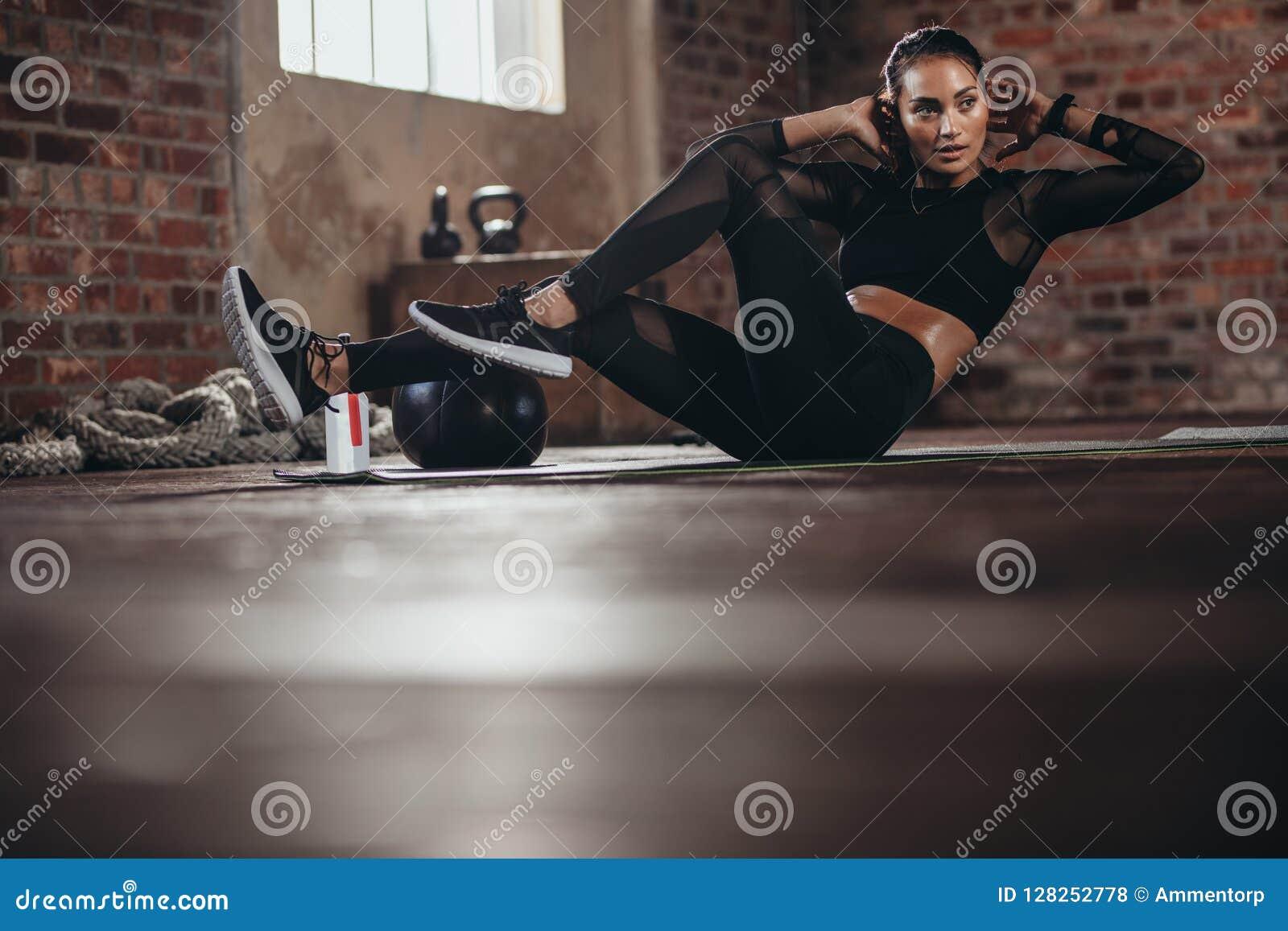 Wijfje in de gymnastiek die abs trainingoefening doen