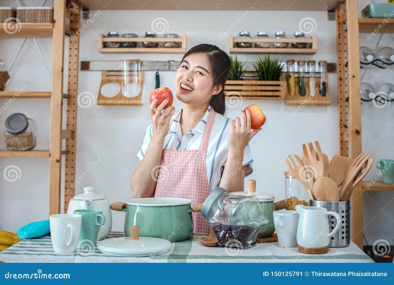 Wijfje die een appel in de keuken houden Portret van een mooi de appel gezond voedsel van de vrouwenholding in de keuken Gelukkig