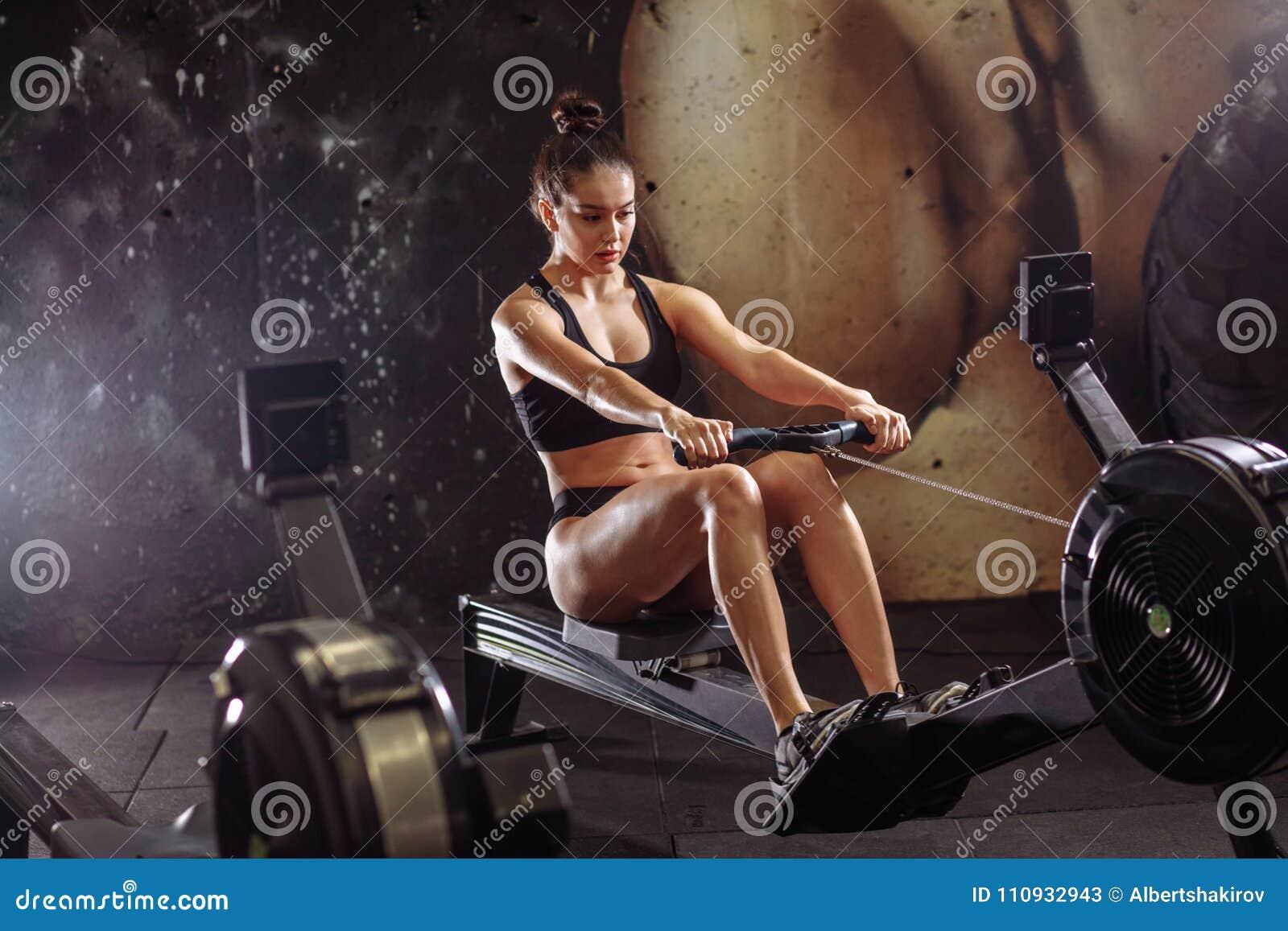 Wijfje die het roeien machine in gymnastiek met behulp van vrouw die cardiotraining in geschiktheidsclub doen
