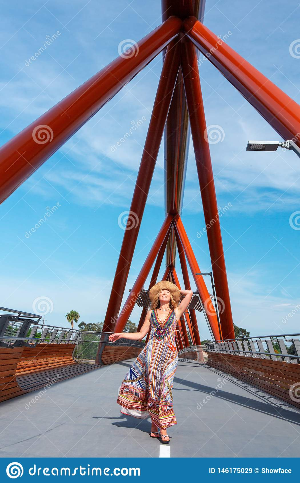 Wijfje die in lange kleding van trillende patronen over Yandhai Nepean lopen die brug kruisen