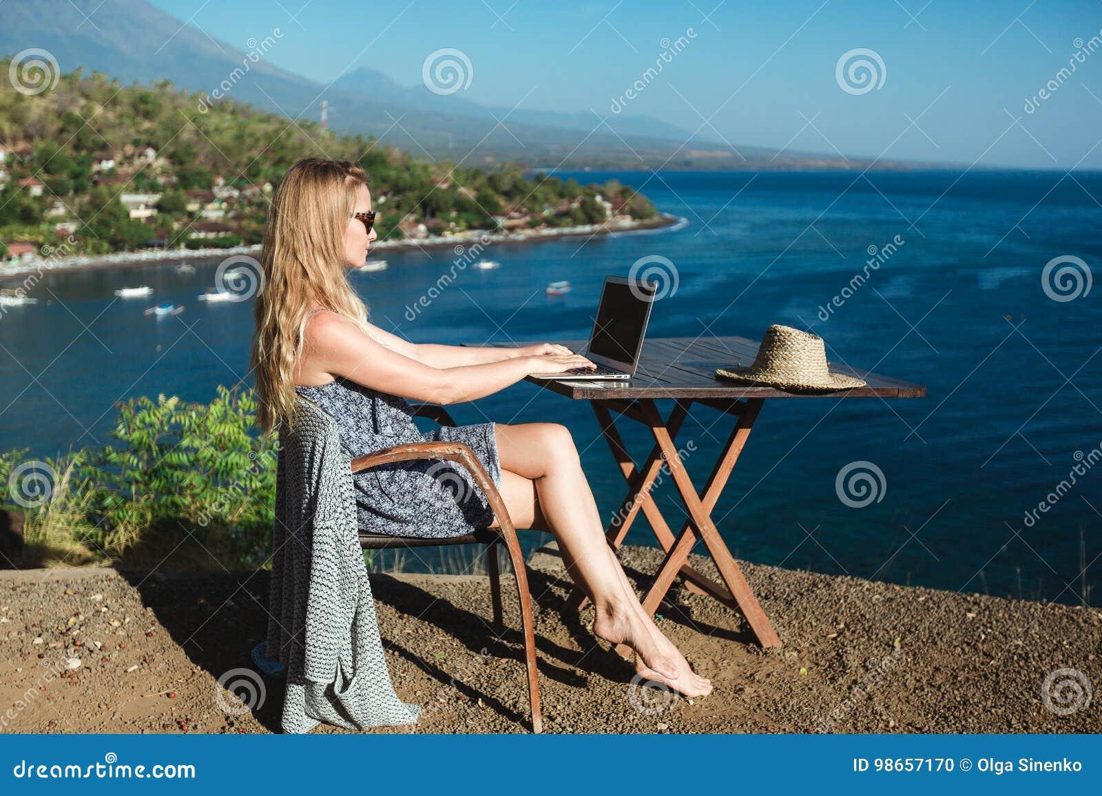 Wijfje die met haar laptop dichtbij het overzees werken