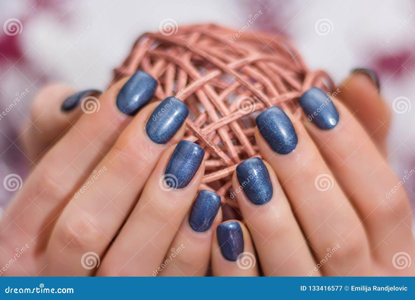 Wijfje die met marineblauw spijkerspoetsmiddel decoratieve streng houden