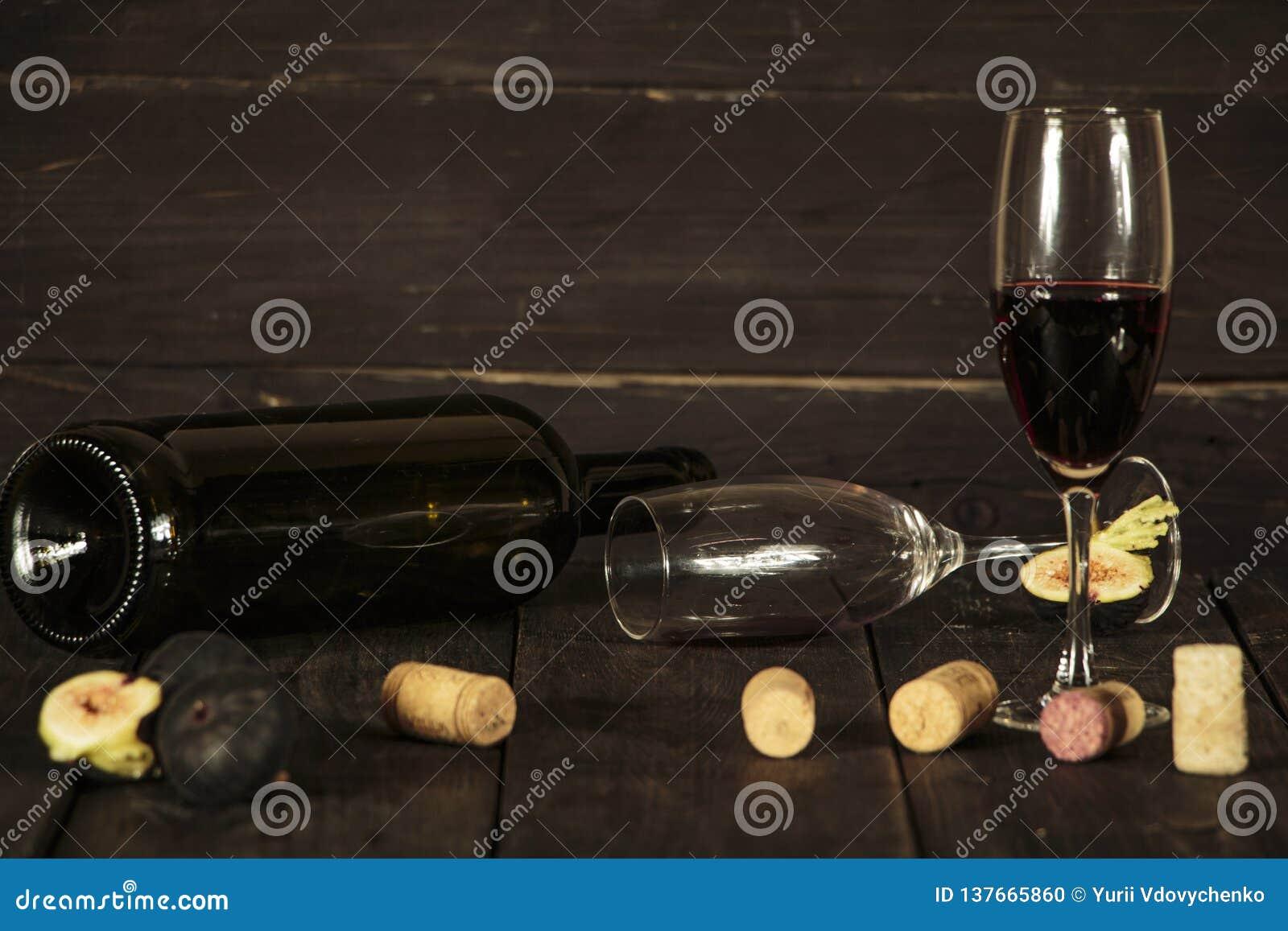 Wijn in een glas een lege fles van fig. op een donkere houten achtergrond Een glas wijn op een houten lijst