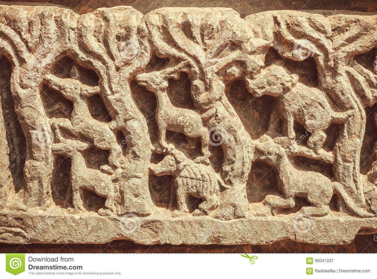 Wild animals and trees of forest on sculpured stone relief