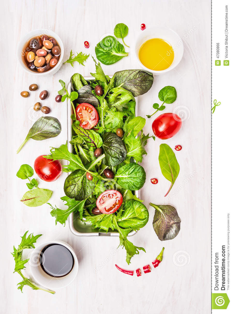 Wild herbs salad with tomatoes,olives,oil and vinegar on white wooden background