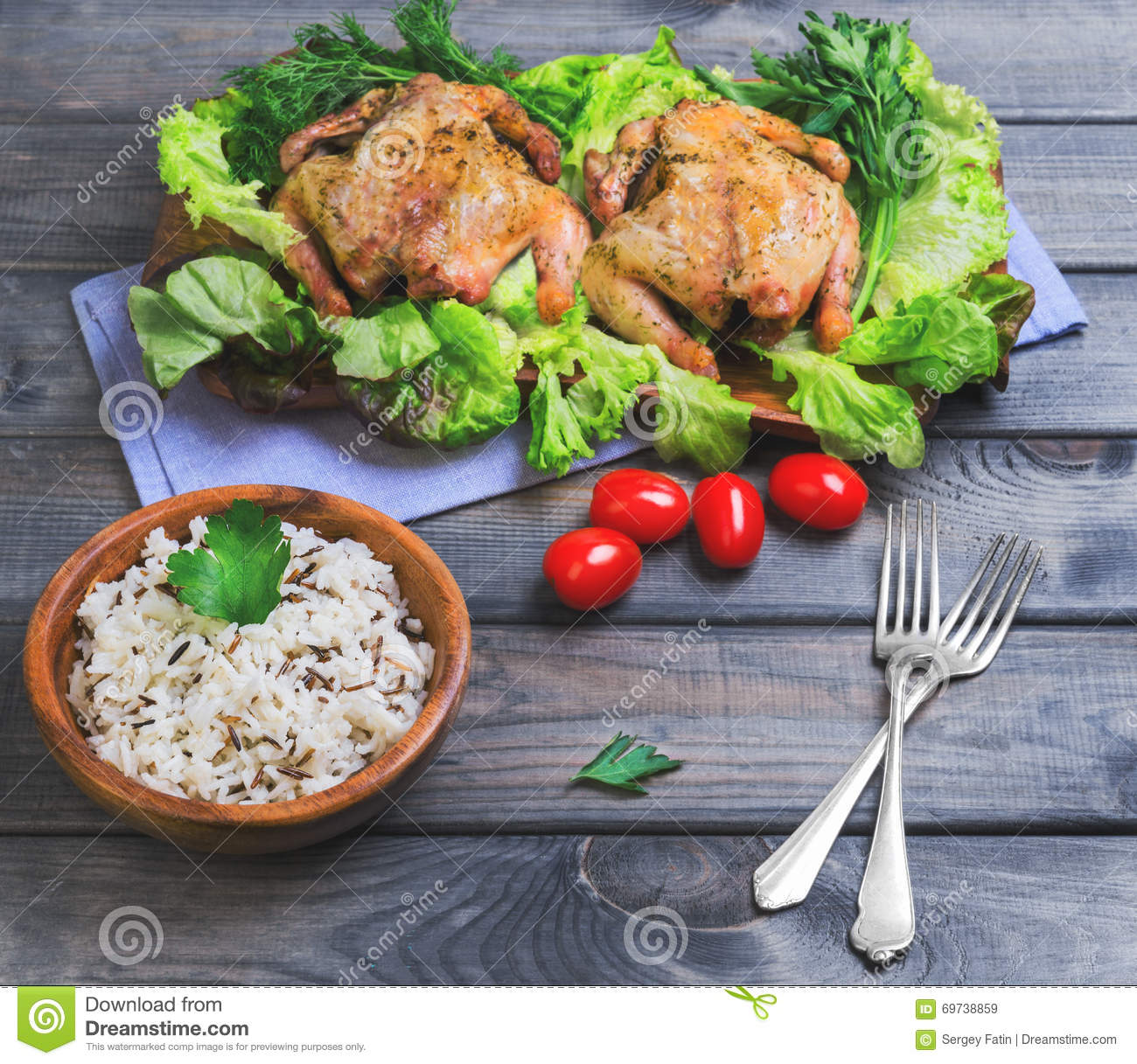 Wild and long grain white rice in a wooden bowl, two baked chick