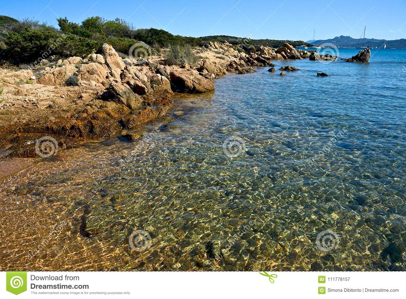 Wild nature seascape with blue water, sandy beach with some rocks