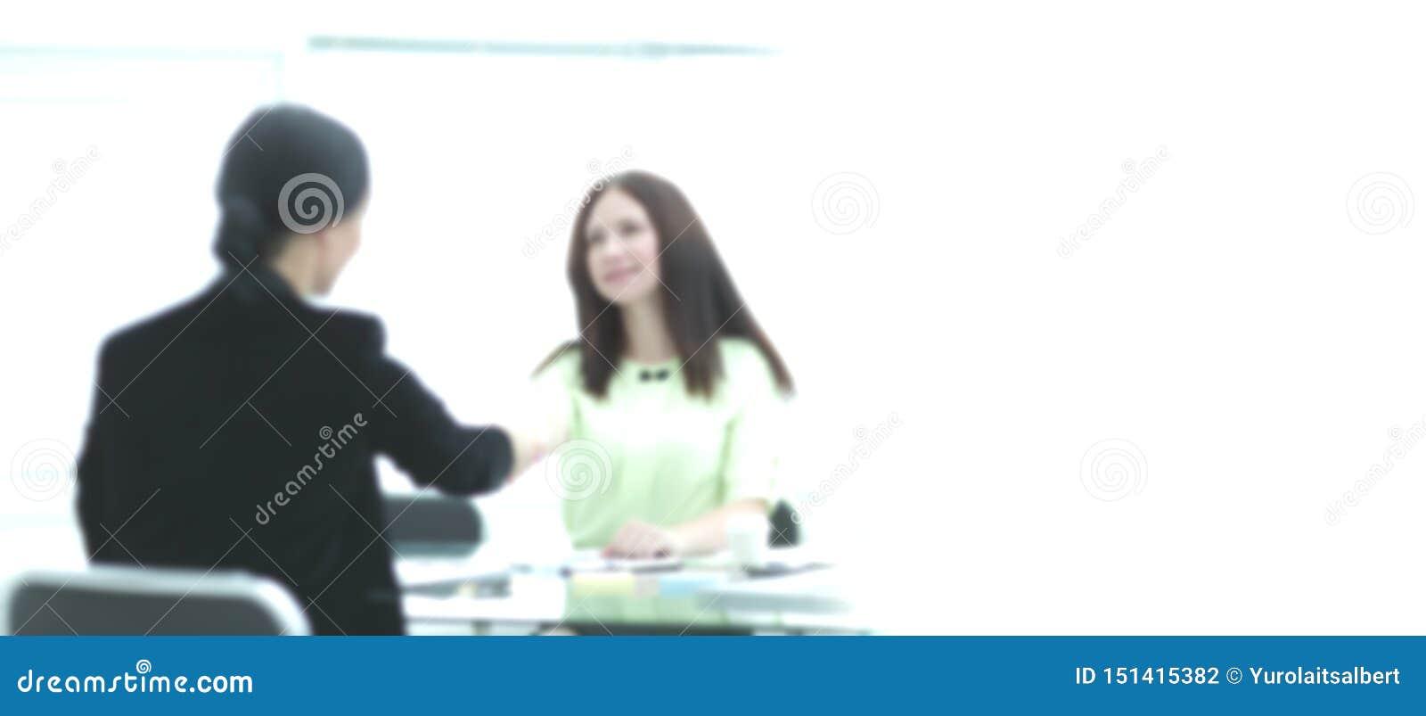Willkommener H?ndedruck von zwei Gesch?ftsfrauen am Schreibtisch Foto mit Kopienraum