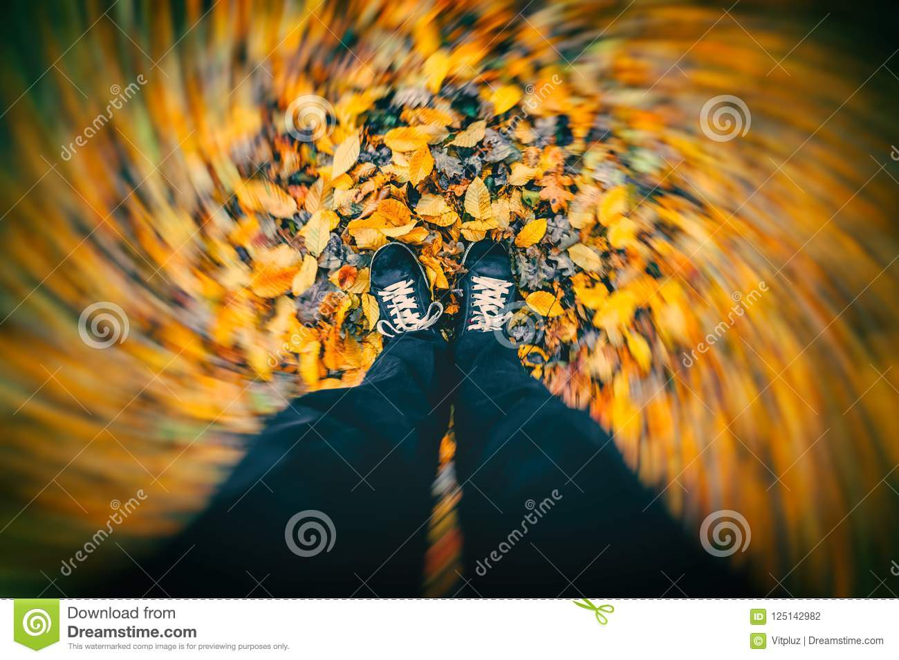 Wind blowing around man standing on dry autumn leaves