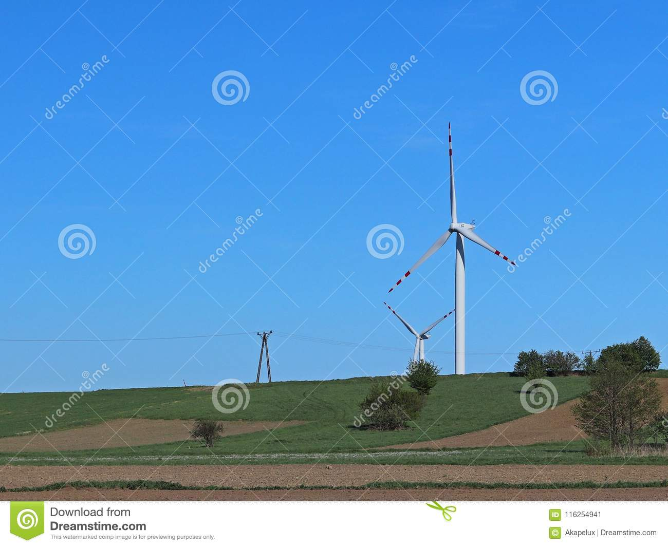 Wind power station in the daytime in the spring. Rotating blades of energy generators. Ecologically clean electricity. Modern tech