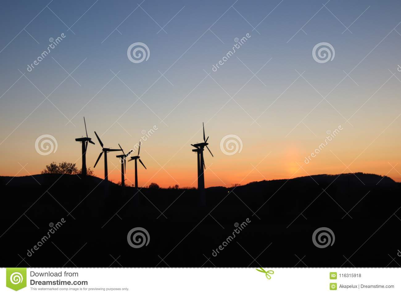 Wind power station in the sunset. Rotating blades of energy generators. Ecologically clean electricity. Modern technologies for t