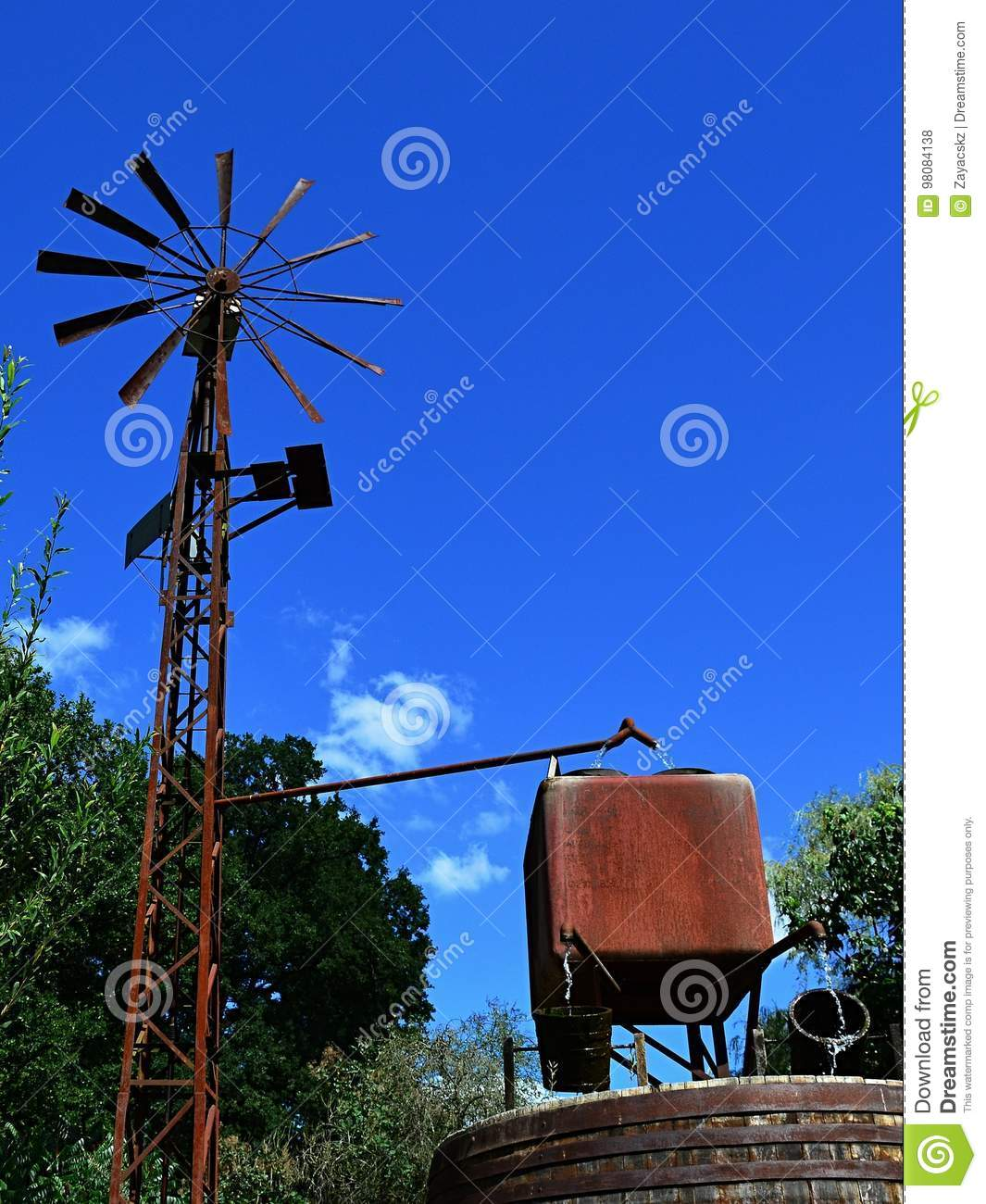 wind powered water pump with rusty pipes rusty square water
