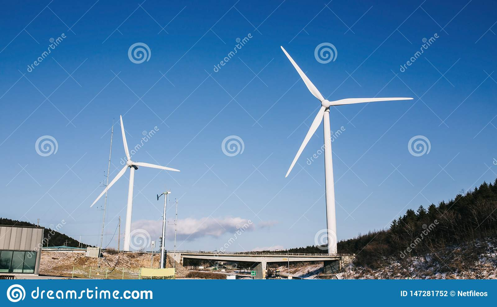 Wind turbine in field and meadow on mountain with beauty blue sky and cloudy background.