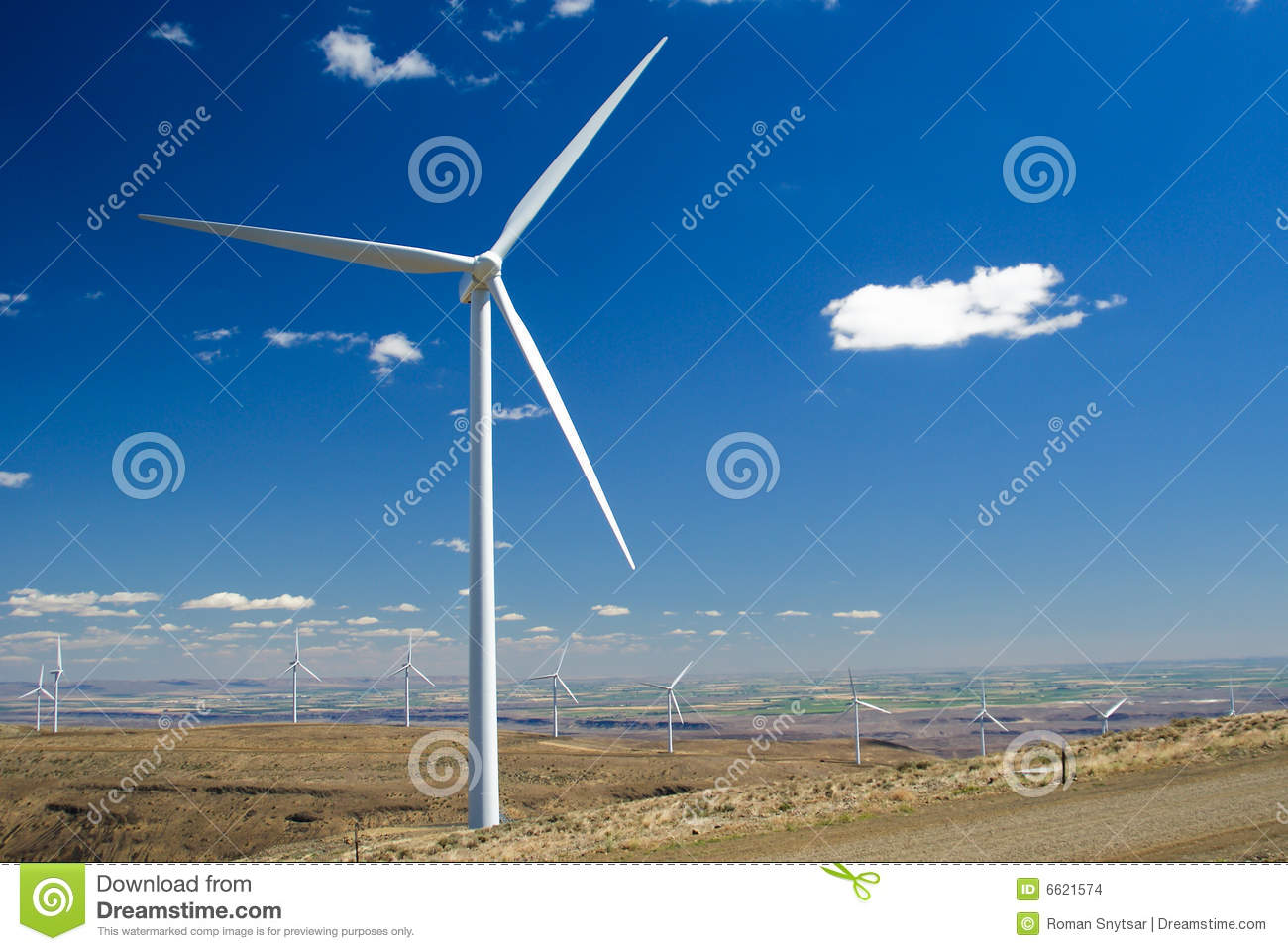 Wind turbine installation with rolling hills and fields in background.