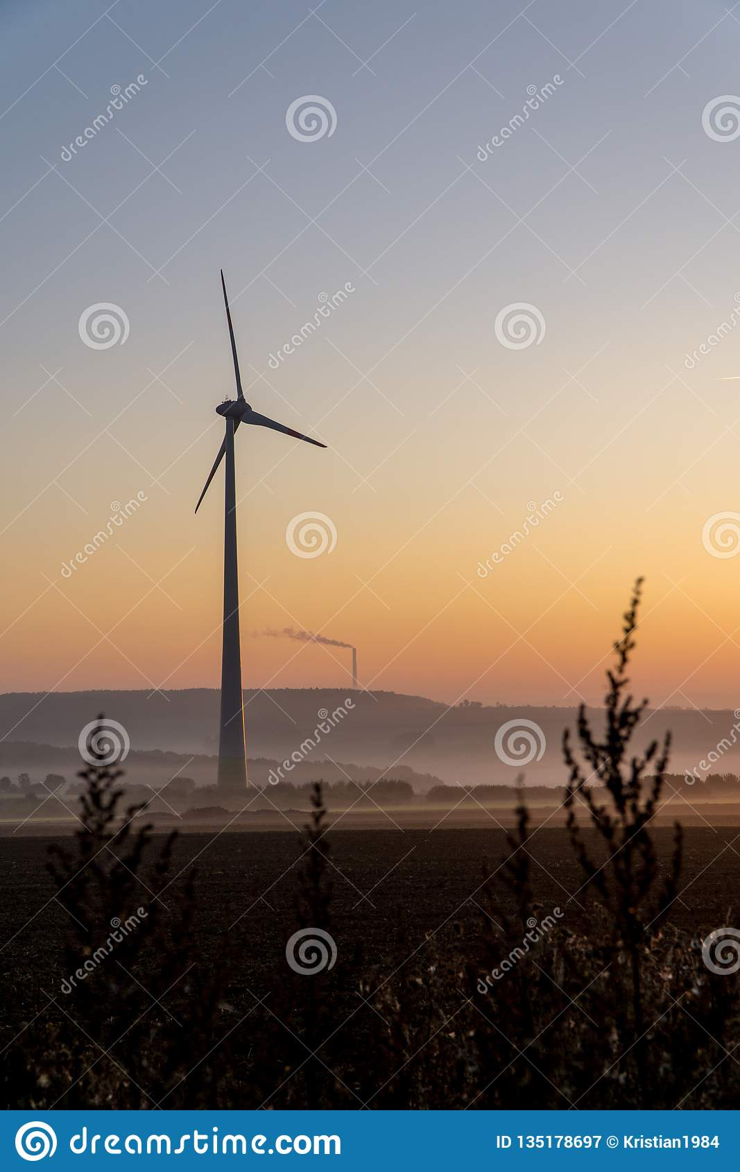 Wind turbines in the morning, partially covered by mist