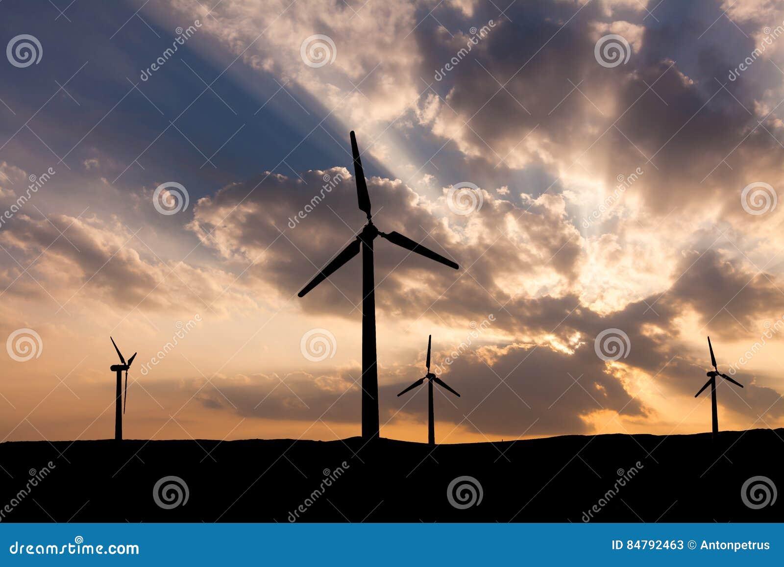 Wind turbines on the sunset sky background