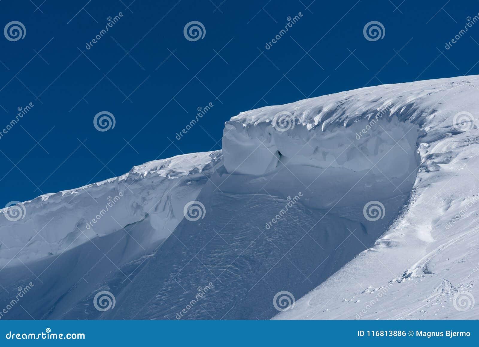 Windblown gebogene Schneekante im Wintersonnenschein